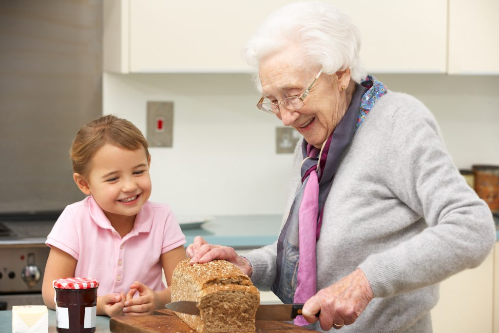 Grandmother and granddaughter preparing food together at home in kitchen